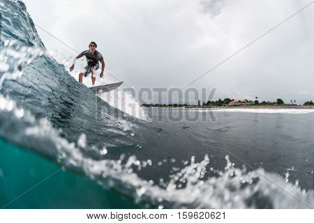 BALI, CANGGU - NOVEMBER 30 2016: Underwater split shot of the young surfer riding the wave in the ocean