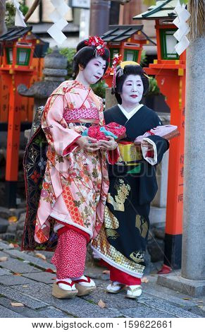 Kyoto, Japan - November 8, 2011: Maiko And Geisha In Traditional Clothes Attending The Annual Kanika