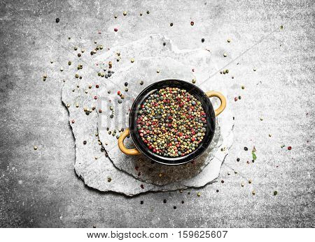 Peppercorn in a bowl on the stone plates . On a stone background.