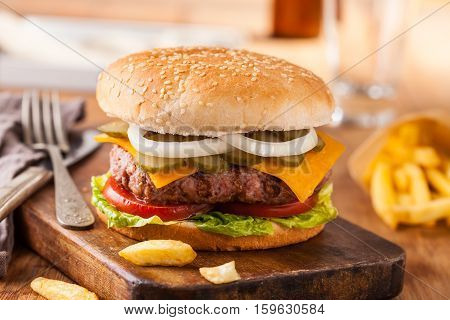 Appetizing hamburger with fries beer on wooden cutting board. Pickles onion and cheddar cheese.