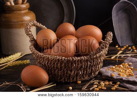Free range eggs in a basket with corn and straw.