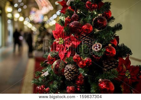 Shopping center with decorated Christmas pine cones, flowers and red balls
