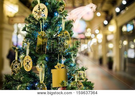 Christmas pine with golden decorations on background of the shopping center