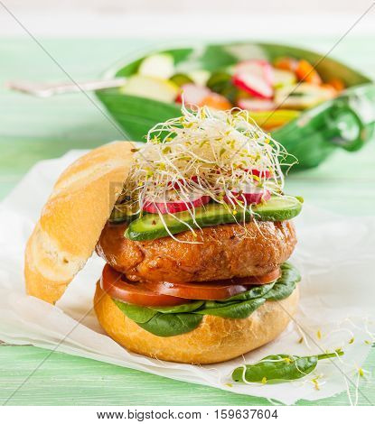 A delicious gourmet hamburger with fresh vegetables: tomato spinach pickles radish and sprouts