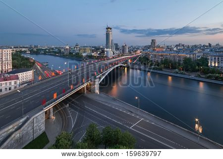 Big Bridge Krasnokholmsky with flags, river, evening quay in Moscow, Russia