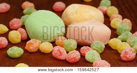 Beautiful colorful japanese mochi rice cakes lying on brown wooden table with red yellow green and orange fruit candy drops around. Shallow DOF. Focus on foreground.
