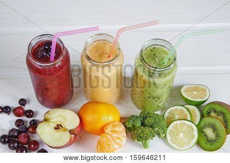 Smoothies of kiwi, mandarin, banana, Lemon, apple, currants, berries on a white background