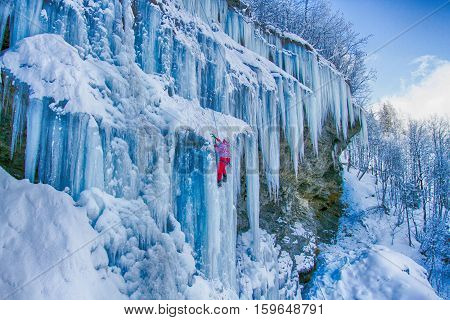 Ice climbing the North Caucasus, man climbing frozen waterfall.
