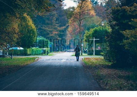Woman walking in autumn towards intersection at dusk. Exel. Achterhoek. Gelderland. The Netherlands.