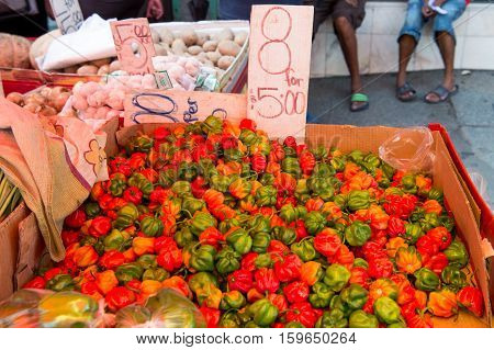 Fresh peppers vegetables ripe agricultural crop displayed for trade outdoors on market on streetscape background