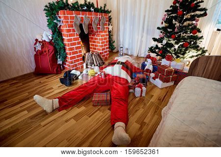Concept of the end the Christmas, New Year. Santa Claus is sleep, drunk in room with a fireplace, tree