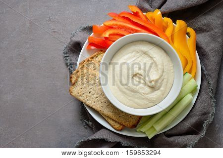 White bean hummus served with fresh vegetable sticks and whole grain crackers view from above space for a text