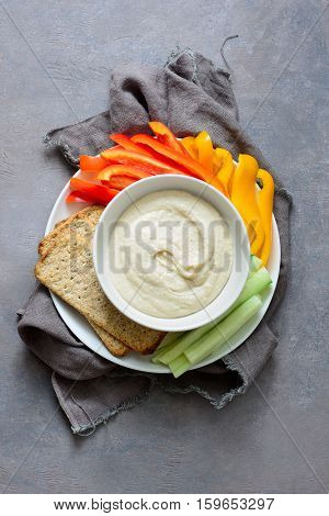 White bean hummus served with fresh vegetable sticks and whole grain crackers view from above