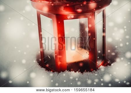 Red candle lantern with candle in snow during snowfall. Christmas Winter New Year background Scenery