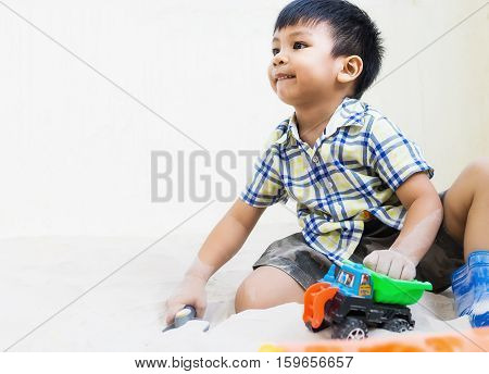 Asian boy is playing in sandbox with copy space