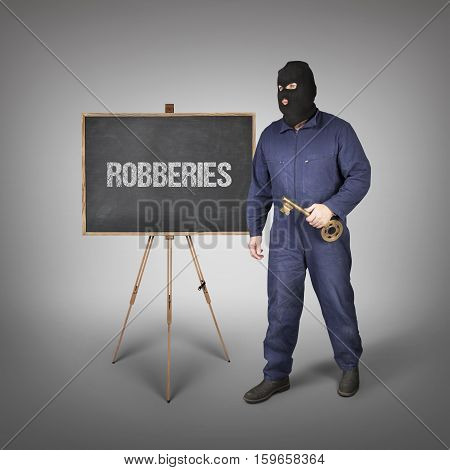 Robberies text on blackboard with thief and key