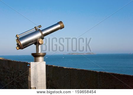 Coin operated viewfinder telescope overlooking sea shore