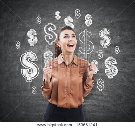 Portrait of an ecstatic businesswoman with an open mouth standing near a blackboard with dollar sign sketches
