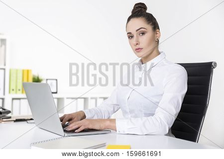 Serious businesswoman is looking at you with contempt while typing at her laptop keyboard