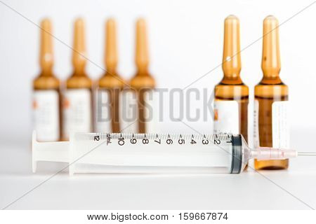Injection syringe and brown ampule background show medicine concept