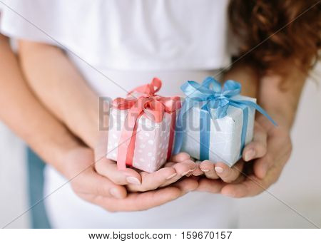 the young family holds a pink and blue gift surprise in hand. young family waiting for baby, hands father and mother keep holding a pink and blue boxes with gifts, newborn boy or girl.