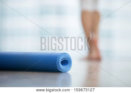 Close up of yoga, fitness, foam exercise mat fix in a roll in living room or fitness center, blurred female body at the background, resting after yoga, fitness class. Healthy lifestyle concept