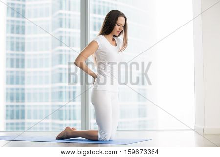 Young frustrated woman in studio trying to reduce stress, relieve aches and pains with yoga help, feeling backpain or unable to perform asanas, rehabilitation after spine trauma, beginner yoga fails