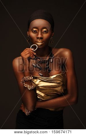 African beautiful woman in gangsta rapper style with gold make-up and jewelry