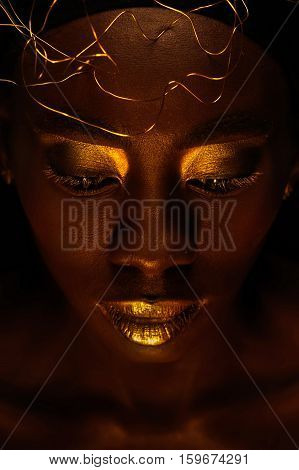 Close up portrait of beautiful african woman with creative gold make-up and jewelry