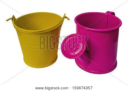 Pink sprinkling can and yellow pail decorative on white background