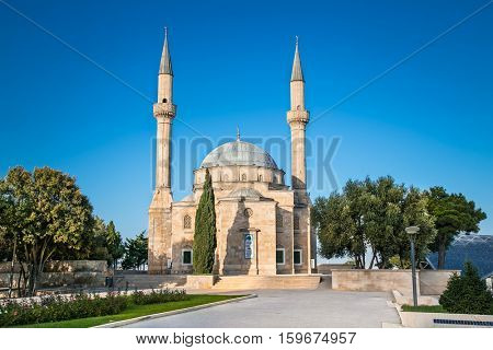 BAKU, AZERBAIJAN - OCT 4, 2016: Mosque of the Martyrs (Sehidler Mescidi Mosque, Turkish Mosque) with the Flame Towers skyscraper in the background in Baku on Oct 4, 2016, Azerbaijan, at sunset.