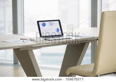 Laptop with graphs on screen on white modern office desk of business analyst, revealing business progress, seeking technology solutions, vacant place. Luxury office interior. Business success concept