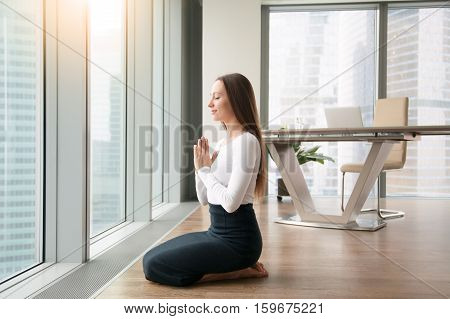 Young woman sitting on her feet knees together, office yoga, practicing seiza vajrasana pose to minimize discomfort of a desk work, making it easier to focus on work, relaxing after serious meeting