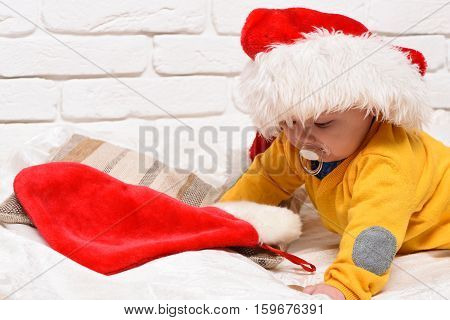 small baby boy with adorable curious face in yellow sweater laying on tummy with dummy in new year hat and christmas or xmas stocking or boot on white brick wall background