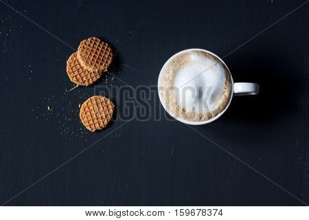 a cup of latte coffee and dutch waffle on a black background