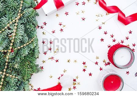 Flat lay Top view Christmas composition on white background. Natural green pine wreath white gift box with red fabric tape Santa cap gold beads spiral ribbon stars confetti candels. Xmas background.