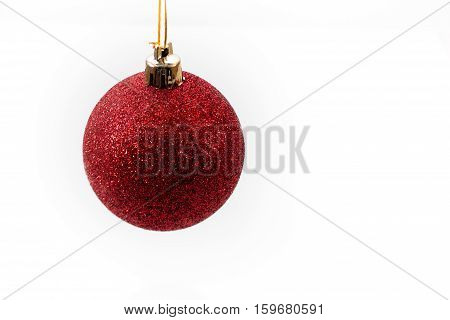Red Christmas ball hanging in midair against a white background