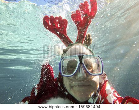 Man with reindeer ears and scuba mask smiling underwater.