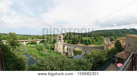 BESALU, CATALONIA, SPAIN - JUNE 17: Summer sun is illuminating bridges and tourists in medieval town on June 17, 2014 in Besalu, Catalonia, Spain.