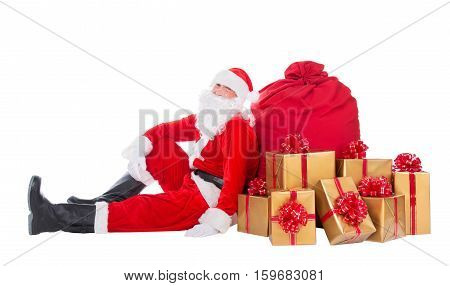 Santa Claus relax sitting near big red Christmas sack full of golden presents gifts and surprises isolated on white background New Year or xmas holiday concept
