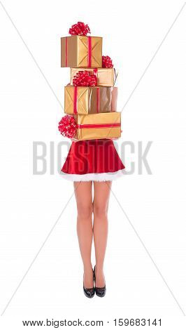 Happy Santa woman with slender legs brings pile of christmas gifts in golden fancy boxes isolated on white background