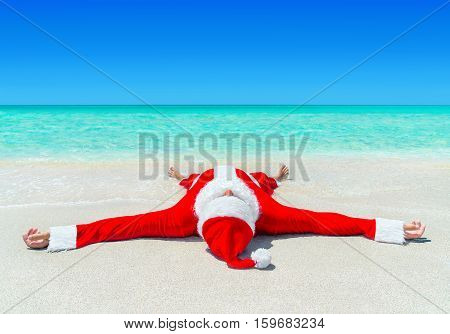 Santa Claus enjoy sunbathing at tropical ocean beach in turquoise waves Christmas and New Year vacation destinations in hot countries concept