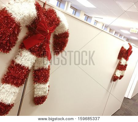 Christmas office Holiday Office Work Cubicles Decorated with Candy Cane Decorations with white room for copy message. Working on orthe holidays, or closed for holiday hours or HR or work party announcements