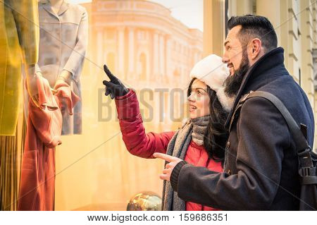 Modern hipster couple shopping on winter cloth pointing moda store window display - Consumerism concept with young fashion people looking for Christmas day present at urban city tour - Focus on woman