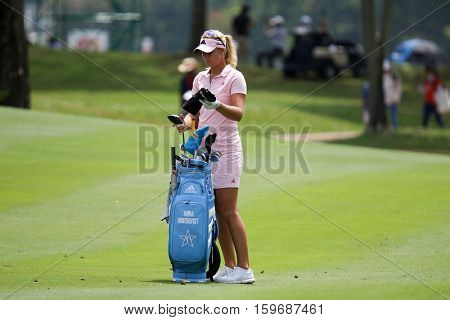 KUALA LUMPUR, MALAYSIA - OCTOBER 29, 2016: Anna Nordqvist of Sweden checks her clubs at the 9th fairway of the TPC Golf Course at the 2016 Sime Darby LPGA Malaysia golf tournament.