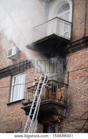 Fire. Lights apartment in high-rise building. Firefighter climbed the fire escape to the balcony. Strong smoke.