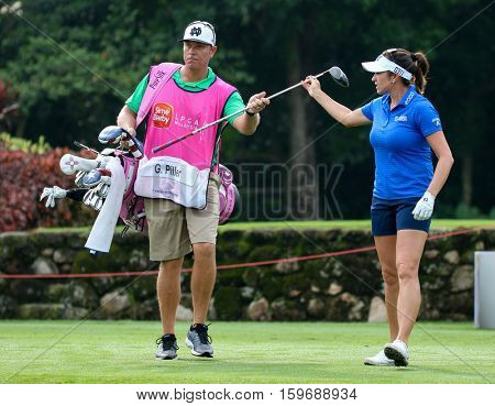 KUALA LUMPUR, MALAYSIA - OCTOBER 29, 2016: Gerina Piller of the USA checks with her caddie on the fairway of the TPC Golf Course at the 2016 Sime Darby LPGA Malaysia golf tournament.
