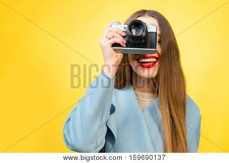 Stylish woman photographer with retro camera on the yellow wall background