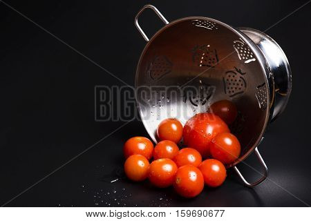 Fresh tomatoes in a metal strainer on a black background
