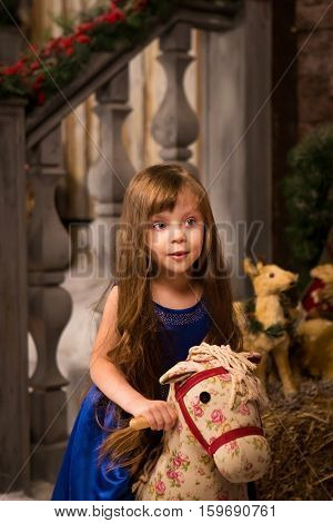 Happy girl in blue dress rides on the toy wooden horse. Christmas and new year concept